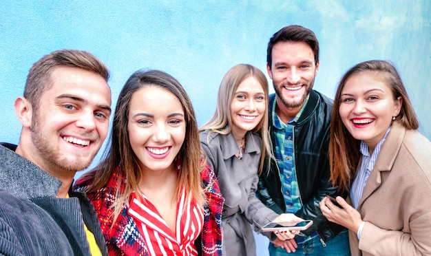 Najlepsi przyjaciele biorący selfie w czterech sezonowych ubraniach