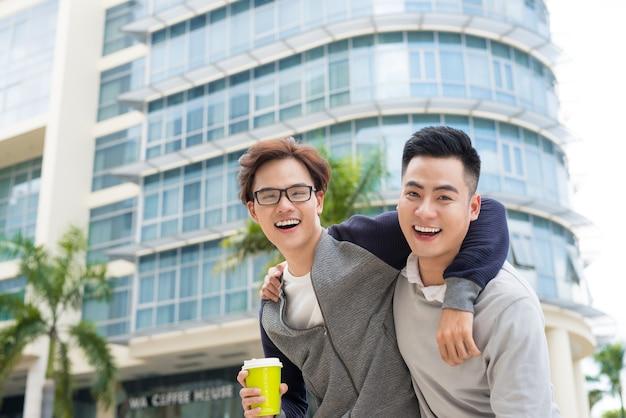 Najlepsi przyjaciele. dwóch facetów przytulających się i spacerujących po mieście.