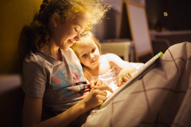 Najlepsi przyjaciele dziewczyn czytają bajkę przed snem. najlepsze książki dla dzieci. siostry czytają książkę w łóżku. rodzinna tradycja.