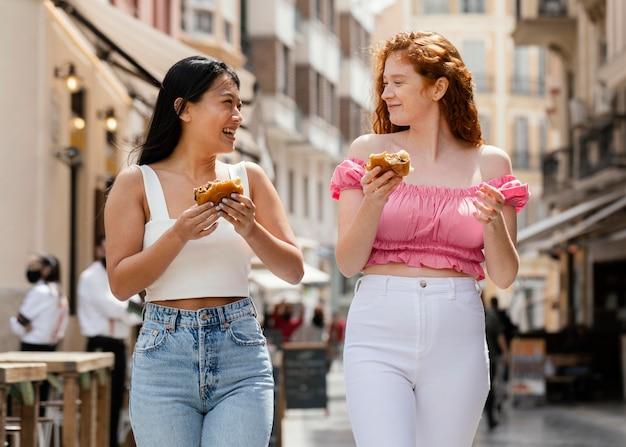 Najlepsi przyjaciele jedzą razem uliczne jedzenie