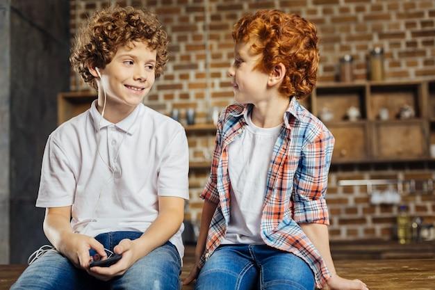 Najlepsi przyjaciele na zawsze. kasztanowy wywietrzony chłopiec patrząc na swojego młodszego brata z radosnym uśmiechem na twarzy, jednocześnie rozmawiając i siedząc na wyspie kuchennej w domu.