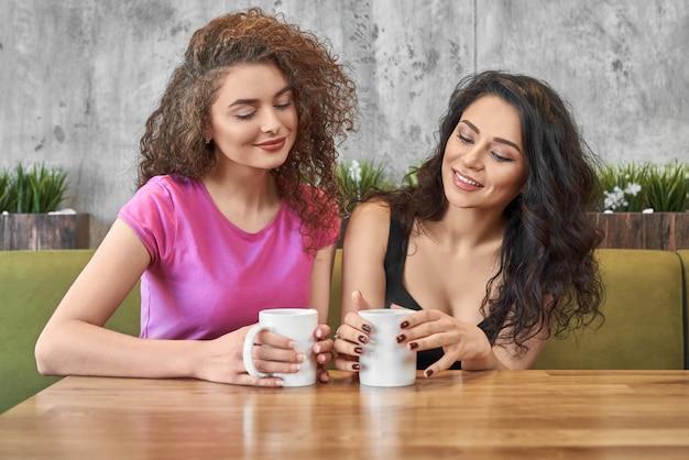 Najlepsi przyjaciele piją herbatę, rozmawiają i spędzają czas w kawiarni