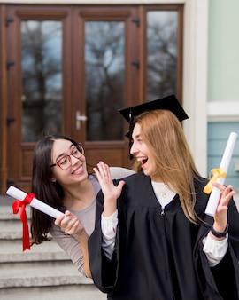 Najlepsi przyjaciele podczas ceremonii ukończenia szkoły na świeżym powietrzu