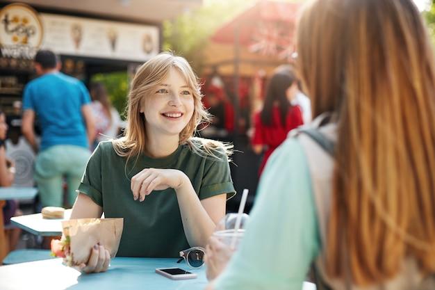 Najlepsi przyjaciele rozmawiają w słoneczny dzień, jedzą tacos w parku lub na targu, uśmiechają się radośnie