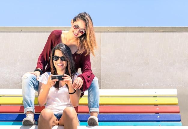 Najlepsi przyjaciele spędzają czas razem na świeżym powietrzu ze smartfonem