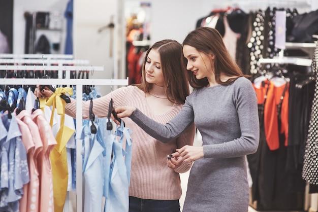 Najlepsi przyjaciele spędzają razem czas. dwie piękne dziewczyny robią zakupy w sklepie odzieżowym. ubrani byli w te same ubrania.