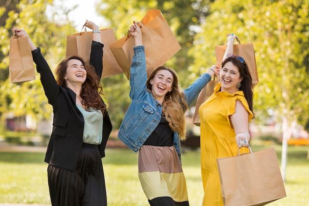Najlepsi przyjaciele trzymając torby na zakupy na zewnątrz