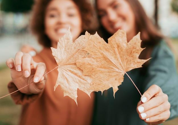 Najlepsi przyjaciele trzymający jesienne liście