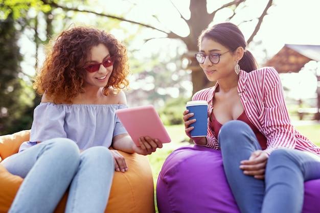 Najlepsi przyjaciele. uśmiechnięta kobieta z kręconymi włosami trzymająca tabletkę i rozmawiająca z przyjaciółką