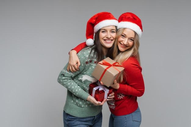 Najlepsi przyjaciele w czapkach mikołaja ze świątecznymi prezentami.