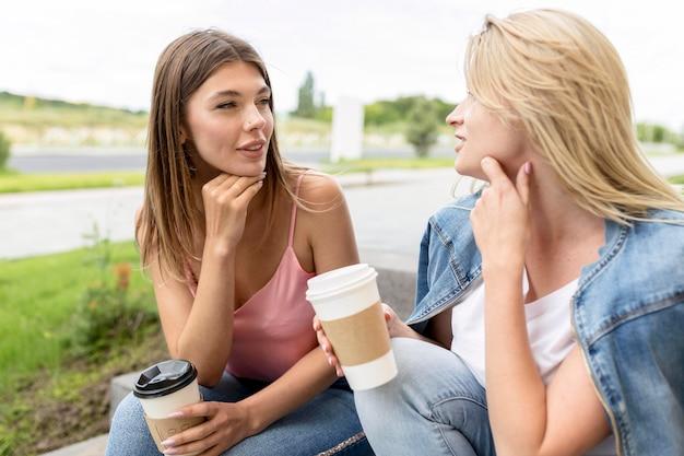 Najlepsi przyjaciele z przodu trzymający papierowe kubki z kawą