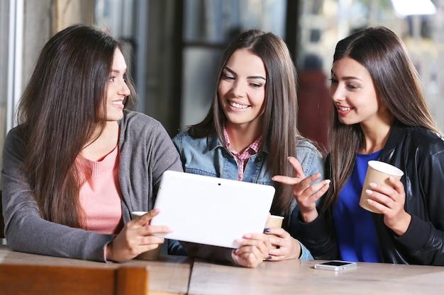 Najlepsi przyjaciele z tabletem razem siedzą na tarasie kawiarni