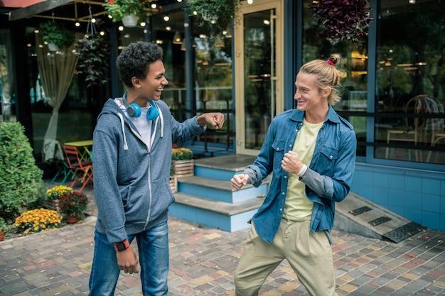 Najlepsi przyjaciele. zachwyceni, szczęśliwi mężczyźni, patrząc na siebie, stojąc razem w pobliżu domu