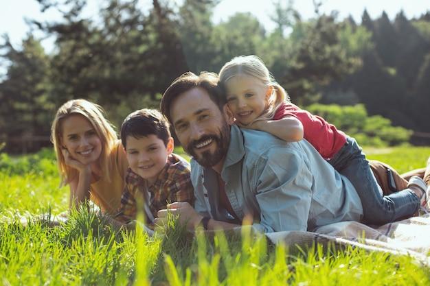 Najlepsi rodzice w historii. radosny brodaty tatuś uśmiechnięty i leżący na okładce z rodziną