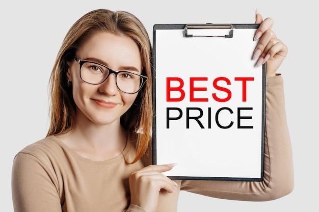 Najlepsza cena. piękna młoda biznesowa kobieta w okularach trzyma makietę schowka na szarym tle