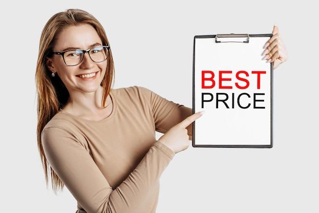 Najlepsza cena. piękna młoda biznesowa kobieta w okularach trzyma schowek z makiety miejsca na białym tle na szarym tle