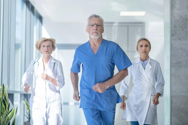 Najlepsza drużyna. grupa zaniepokojonych lekarzy biegnąca korytarzem szpitala