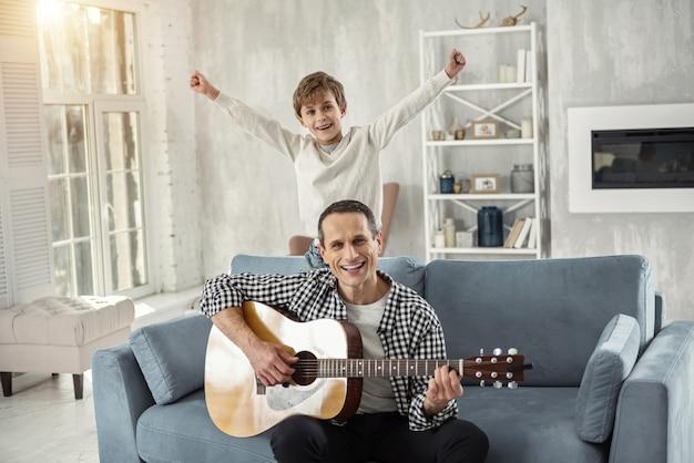 Najlepsza drużyna. przystojny, zachwycony ciemnowłosy mężczyzna uśmiecha się i gra na gitarze, a jego syn stoi za nim na kanapie i uśmiecha się