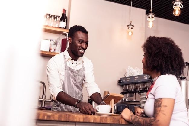 Najlepsza kawa. radosny miły człowiek uśmiechnięty, serwując kawę klientowi