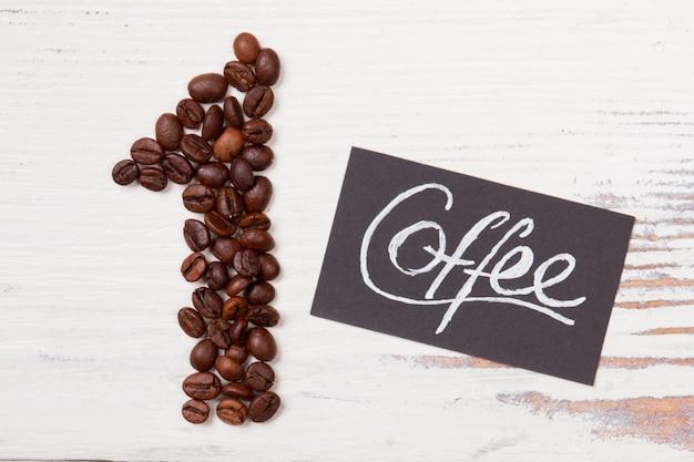 Najlepsza koncepcja kawy. wybór klientów. numer jeden zrobiony z ziaren kawy i papieru z napisem kawy leżącym na białym drewnie.