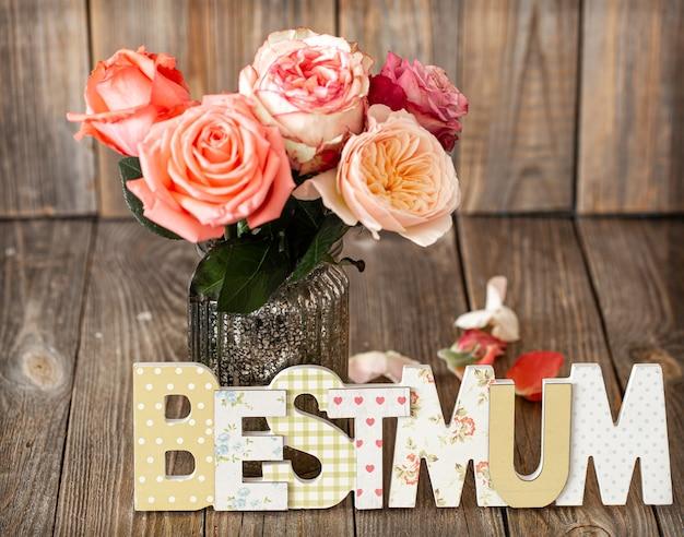 Najlepsza mama napisana wielobarwnymi drewnianymi literami i świeża róża w szklanym wazonie.