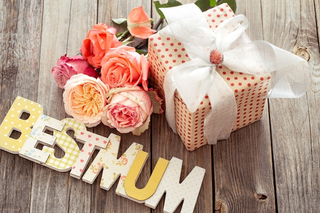 Najlepsza mama napisana wielobarwnymi drewnianymi literami, prezent i świeża róża. szczęśliwego dnia matki