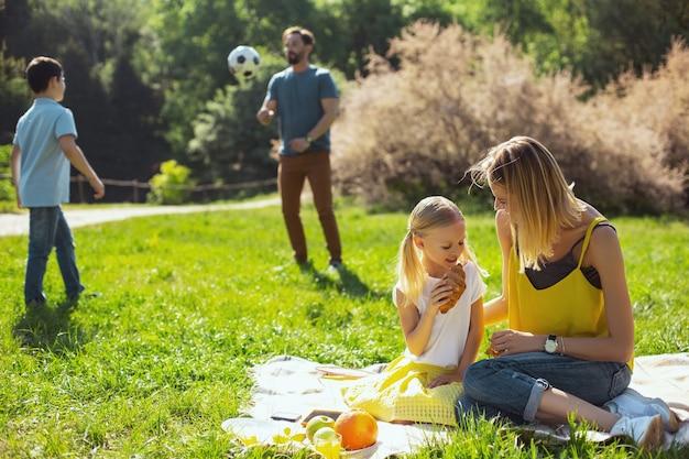 Najlepsza matka. radosna kochająca mama siedzi z córką i mężem bawiąc się z synem