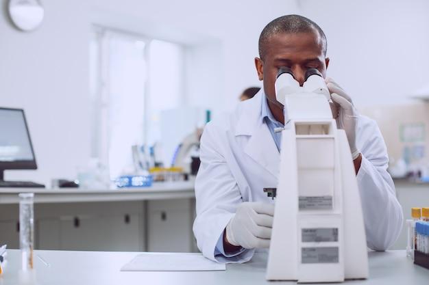 Najlepsza praca w historii. inteligentny, doświadczony badacz pracujący nad swoim mikroskopem podczas pracy w laboratorium