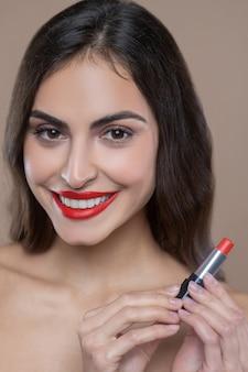 Najlepsza szminka. zadowolona twarz ciemnowłosej kobiety z czerwoną szminką na ustach trzymająca walizkę w dłoniach