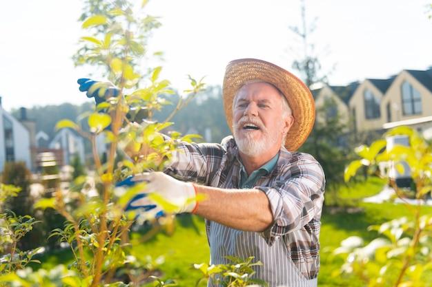 Najlepsze hobby. zainspirowany miły człowiek cieszący się dniem podczas pracy w ogrodzie