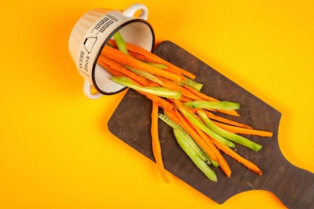 Najlepsze marchewki i ogórki wbijają na drewnianą deskę do krojenia na żółtym