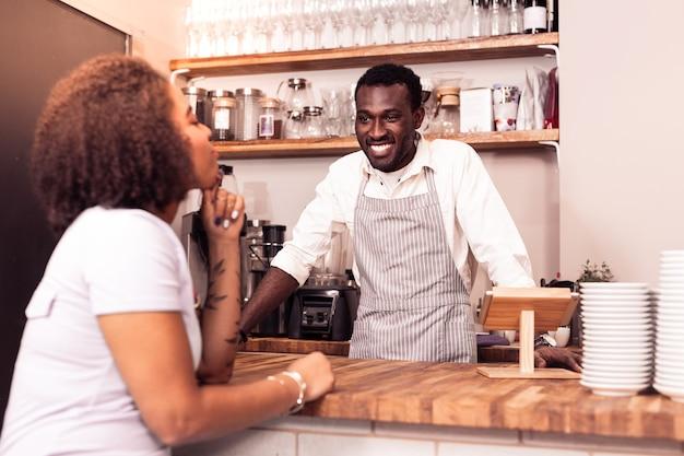 Najlepsze miejsce na kawę. radosny miły człowiek uśmiechający się do klienta podczas pracy w stołówce