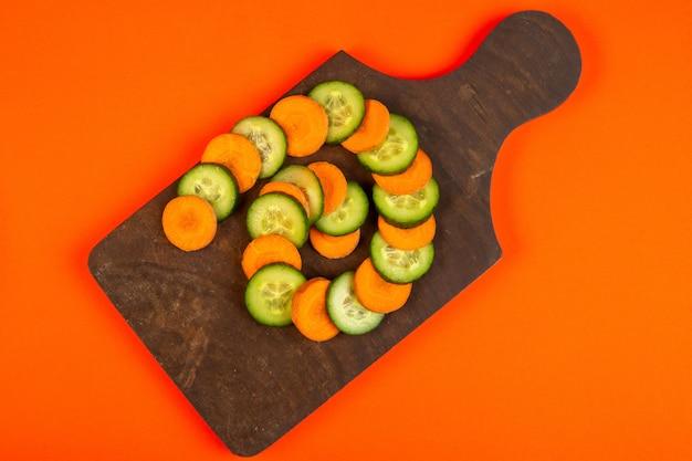 Najlepsze plasterki marchewki i ogórka na drewnianej desce do krojenia na pomarańczowo