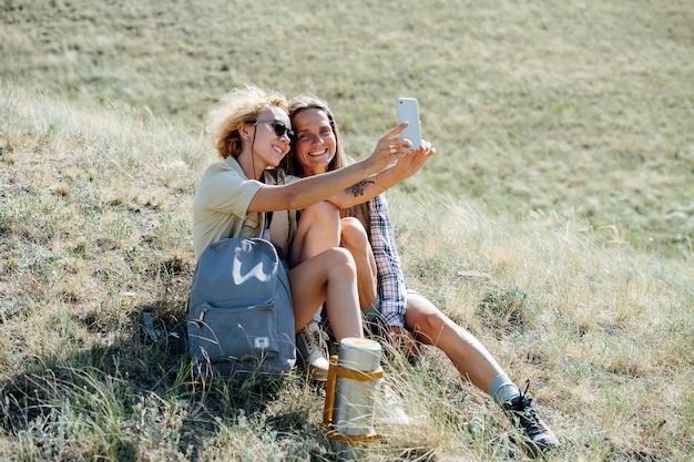 Najlepsze przyjaciółki siedzi na zboczu suchej trawy, biorąc selfie, uśmiechając się. siedząc blisko siebie.