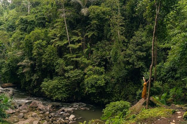 Najlepsze wakacje. wesoła brunetka unosi ramiona, ciesząc się wolnością w dzikiej przyrodzie