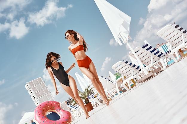 Najlepsze wspomnienia zaczynają się tutaj dziewczyny bawiące się na basenie na dachu