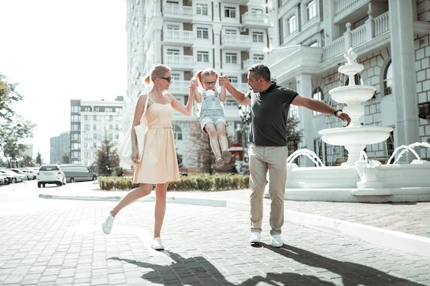 Najlepszy czas. szczęśliwi rodzice trzymający się za ręce córeczki podnoszącej ją podczas porannego spaceru.