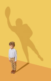 Najlepszy członek zespołu. koncepcja dzieciństwa i marzeń. koncepcyjne obraz z dzieckiem i cieniem na żółtej ścianie studia. mały chłopiec chce zostać amerykańskim piłkarzem i zbudować karierę sportową.