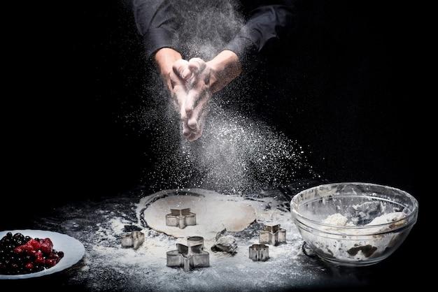 Najlepszy deser. zbliżenie na ręce młodych mans przygotowywania plików cookie podczas korzystania z form piekarniczych i pracy w restauracji.