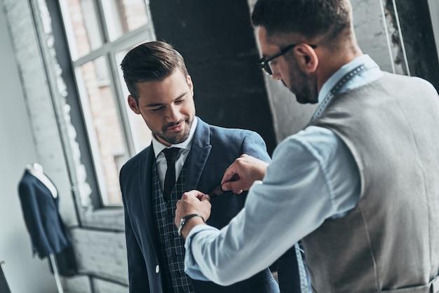 Najlepszy garnitur. młody modny projektant pomagający swojemu klientowi się ubrać