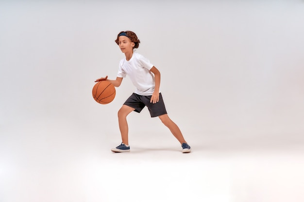 Najlepszy sport dla dzieci pełnometrażowe ujęcie nastoletniego chłopca grającego w koszykówkę, stojąc na białym tle