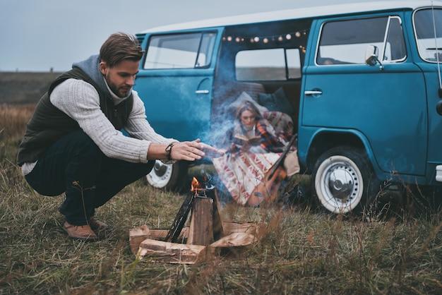 Najlepszy sposób na utrzymanie ciepła. piękna młoda kobieta czyta książkę, podczas gdy jej chłopak rozgrzewa się przy ognisku