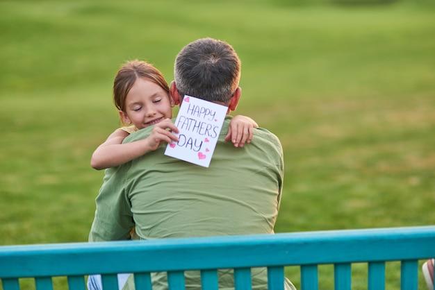 Najlepszy tata kiedykolwiek urocza dziewczynka przytula swojego tatę, witając go i dając ręcznie robioną pocztówkę