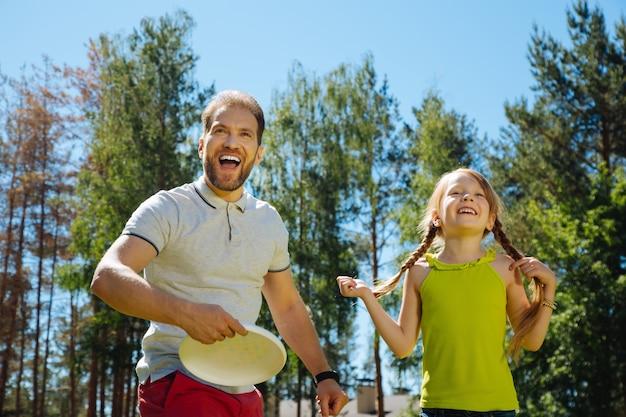 Najlepszy tatuś. zadowolony kochający ojciec, uśmiechnięty i grający w grę ze swoimi dziećmi