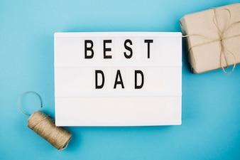 Najlepszy tytuł taty na tablecie w pobliżu obecnego pudełka i nici