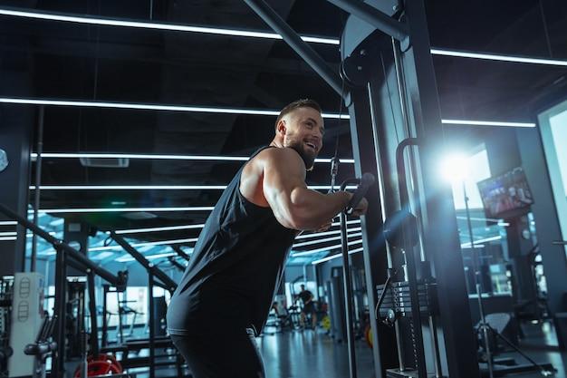 Najlepszy wybór. młody muskularny kaukaski sportowiec trenuje na siłowni, robi ćwiczenia siłowe, ćwiczy, pracuje nad górną częścią ciała z ciężarkami i sztangą. fitness, wellness, koncepcja zdrowego stylu życia.