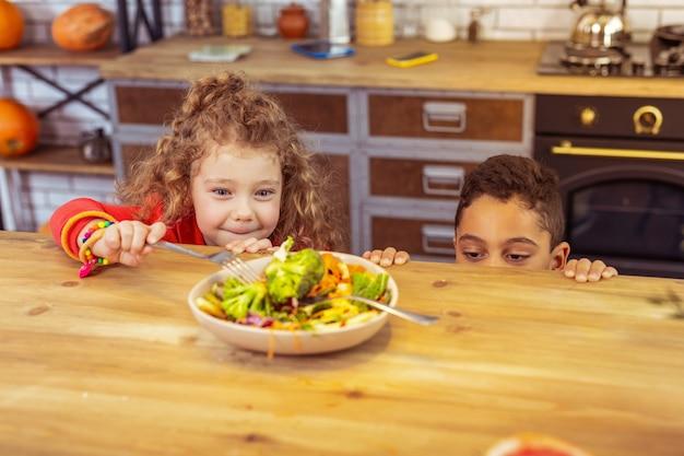 Najlepszy wybór. śliczna mała kobieta utrzymująca uśmiech na twarzy, patrząc na brokuły