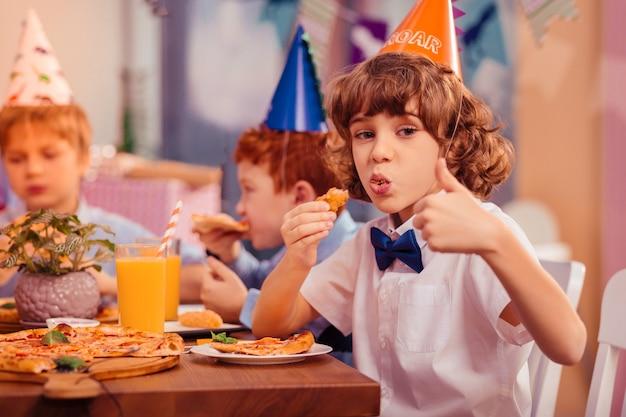 Najlepszy wybór. zadowolony dzieciak je pizzę będąc w kawiarni z przyjaciółmi