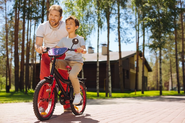 Najlepszym nauczycielem. zaalarmowany kochający ojciec uśmiecha się i uczy syna jeździć na rowerze