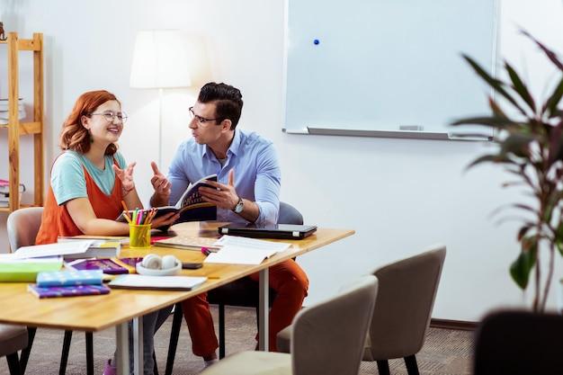 Najlepszym nauczycielem. zachwycona rudowłosa kobieta uśmiecha się podczas prywatnej lekcji